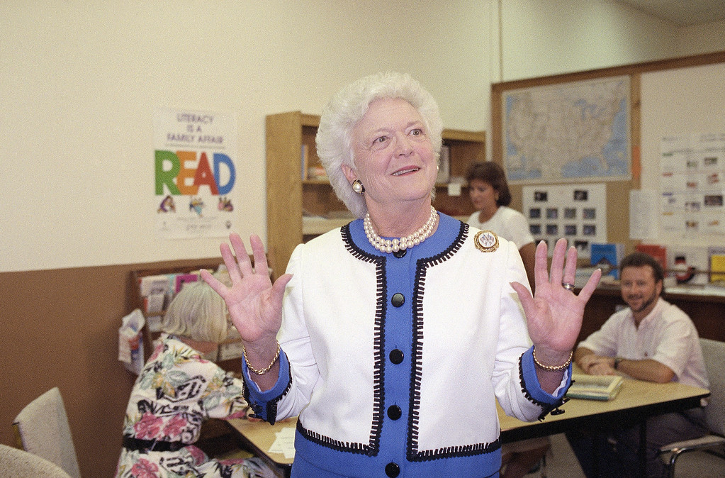 . First Lady Barbara Bush, center, expresses her pleasure that the Pres. George H. W. Bush was released from Bethesda Naval Medical, when asked about his health by reporters following a tour of the Martin County Literacy Council, Monday, May 7, 1991, Stuart, Fla. The First Lady met with volunteers and students at the center. (AP Photo/Lynne Sladky)