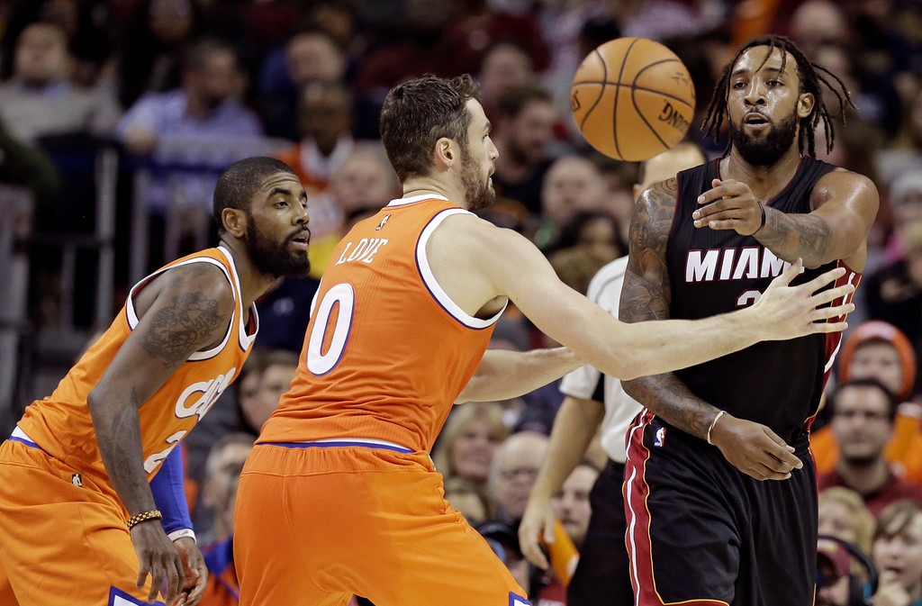 . Miami Heat\'s Derrick Williams, right, passes around Cleveland Cavaliers\' Kyrie Irving and Kevin Love in the first half of an NBA basketball game Friday, Dec. 9, 2016, in Cleveland. (AP Photo/Tony Dejak)