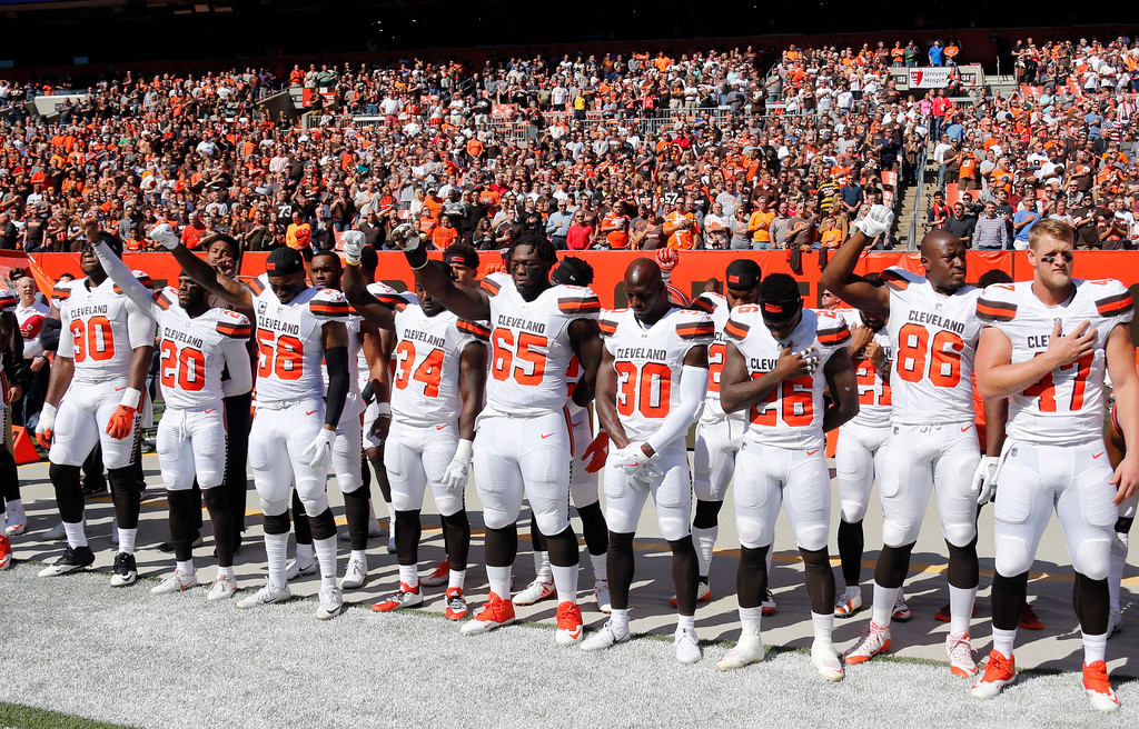 . Some Cleveland Browns hold up their fists during the national anthem before an NFL football game against the Cincinnati Bengals, Sunday, Oct. 1, 2017, in Cleveland. (AP Photo/Ron Schwane)