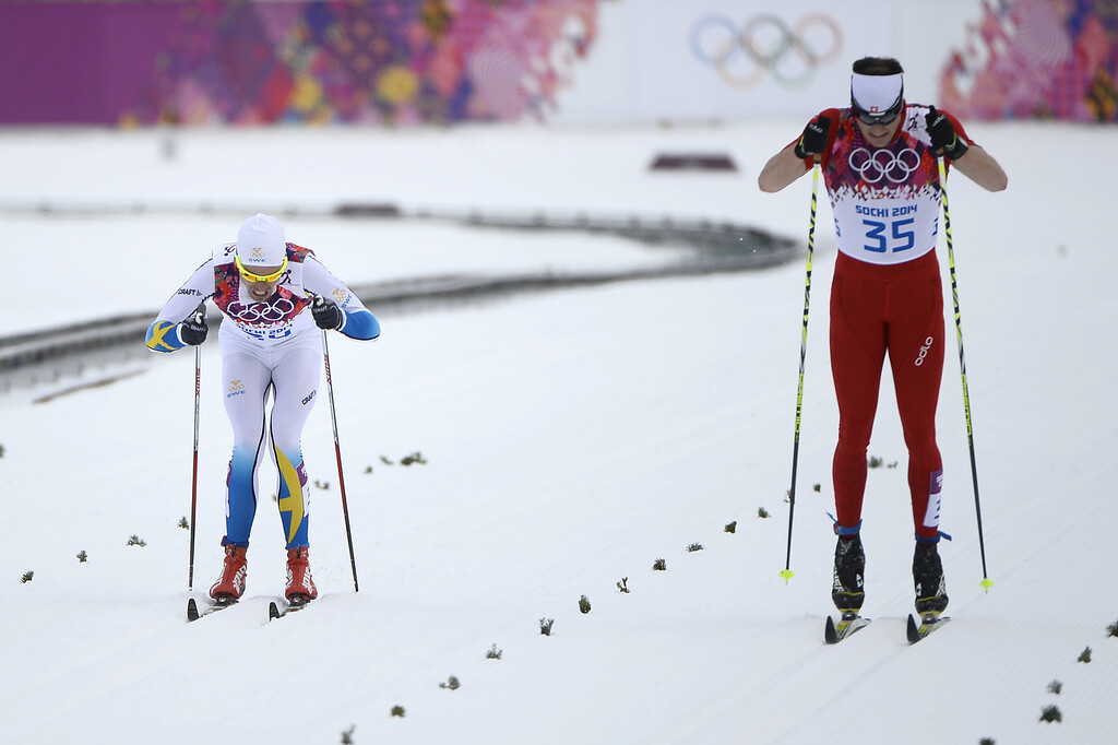 . Silver medalist Sweden\'s Johan Olsson (34) and gold medalist Switzerland\'s Dario Cologna (35) race to cross the finish line in the Men\'s Cross-Country Skiing 15km Classic at the Laura Cross-Country Ski and Biathlon Center during the Sochi Winter Olympics on February 14, 2014 in Rosa Khutor near Sochi.  AFP PHOTO / PIERRE-PHILIPPE MARCOU/AFP/Getty Images