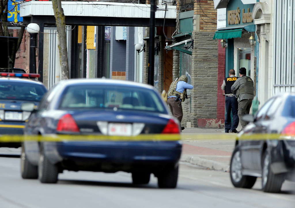 . Law enforcement officers take cover along Main Street when shots were fired while they were searching for a suspect in two shootings that killed four and injured at least  two on, Wednesday, March 13, 2013, in Herkimer, N.Y.   (AP Photo/Mike Groll)