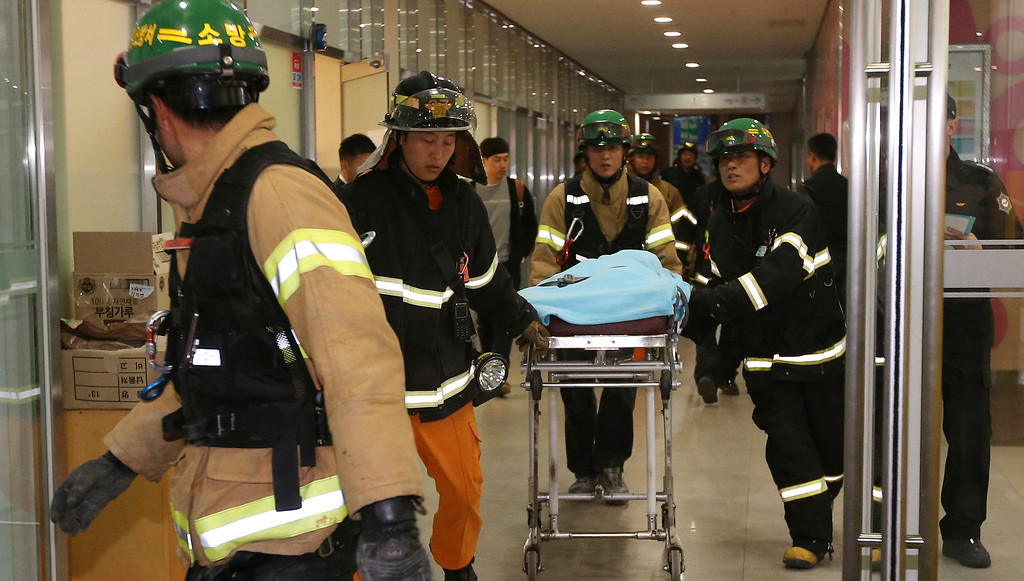 . Rescue workers carry an injured person on a stretcher after a ventilation grate was collapsed at an outdoor theater in Seongnam, south of Seoul, South Korea, Friday, Oct. 17, 2014.  (AP Photo/Yonhap, Shin Young-geun)