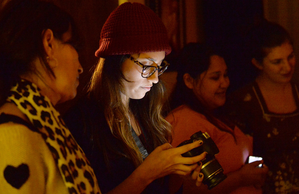 . Miriam Valenzuela watches her daughter, Lizeth, go through pictures as Midwife Simona Istrate guides Lilibeth and Luis Salas, of El Monte, through the birth of their son, Nicholas, by water birth at the Natural Birth Center and Women\'s Wellness in Whittier on December 29, 2013. Birthing centers and home births are becoming more popular and the Birth Center in Whittier is doing so well it opened a second office in Beverly Hills. (Staff Photo by Keith Durflinger/Whittier Daily News)