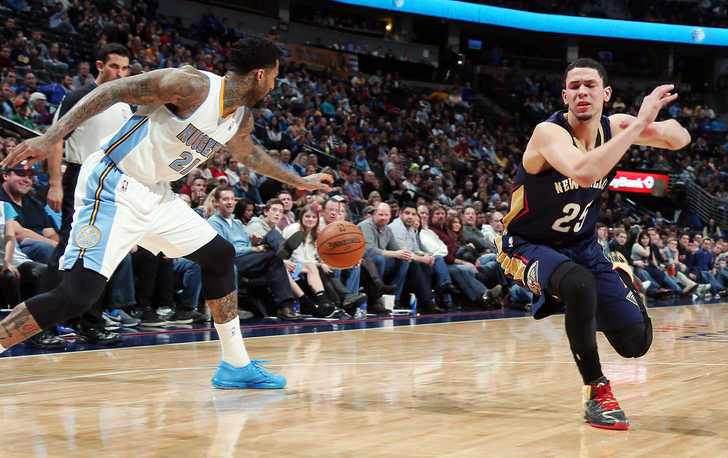 . New Orleans Pelicans guard Austin Rivers, right, reacts after losing the ball to Denver Nuggets forward Wilson Chandler in the fourth quarter of the Nuggets\' 102-93 victory in an NBA basketball game in Denver on Sunday, Dec. 15, 2013. (AP Photo/David Zalubowski)