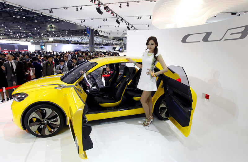 . A model poses next to Kia Motors\' four-door coupe compact, CUB at the Seoul motor show in Goyang, north of Seoul March 28, 2013. South Korea\'s Kia Motors is worried about the sharp decline in the value of the yen, which is aiding Japanese rivals, an executive at the affiliate of Hyundai Motor said on Thursday.  REUTERS/Lee Jae-Won