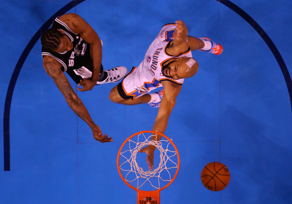 . OKLAHOMA CITY, OK - MAY 25: Derek Fisher #6 of the Oklahoma City Thunder goes up for the ball against Kawhi Leonard #2 of the San Antonio Spurs in the second half during Game Three of the Western Conference Finals of the 2014 NBA Playoffs at Chesapeake Energy Arena on May 25, 2014 in Oklahoma City, Oklahoma.  (Photo by Ronald Martinez/Getty Images)