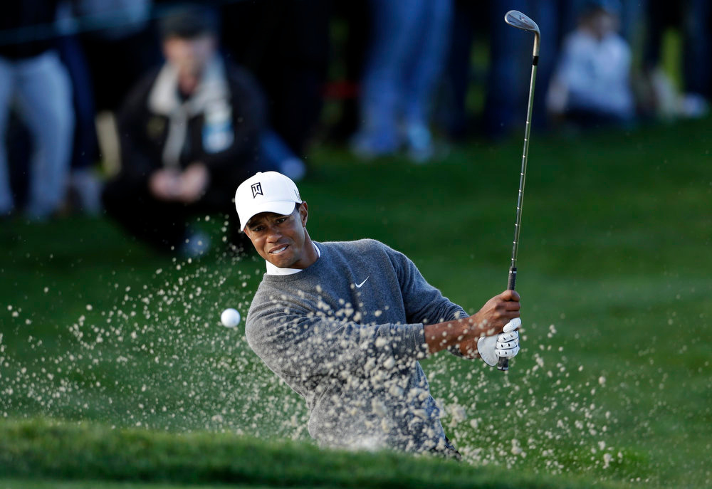 Description of . Tiger Woods hits out of a bunker on the fifth hole during the fourth round of the Farmers Insurance Open golf tournament at the Torrey Pines Golf Course, Sunday, Jan. 27, 2013, in San Diego. (AP Photo/Gregory Bull)