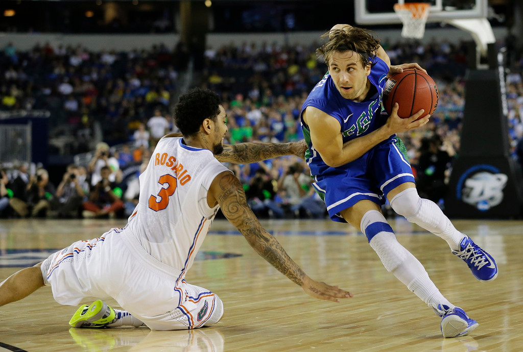 . Florida Gulf Coast\'s Christophe Varidel drives around Florida\'s Mike Rosario (3) during the first half of a regional semifinal game in the NCAA college basketball tournament, Friday, March 29, 2013, in Arlington, Texas. (AP Photo/Tony Gutierrez)