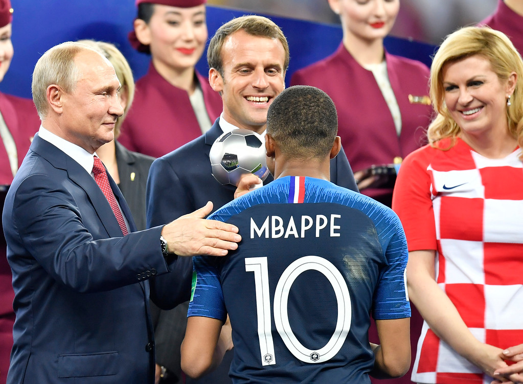 . Russian President Vladimir Putin, French President Emmanuel Macron and Croatian President Kolinda Grabar-Kitarovic, from left, award France\'s Kylian Mbappe as best young player after the final match between France and Croatia at the 2018 soccer World Cup in the Luzhniki Stadium in Moscow, Russia, Sunday, July 15, 2018. (AP Photo/Martin Meissner)