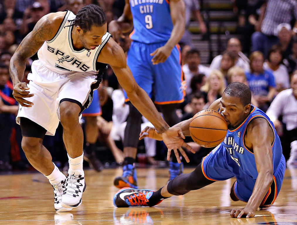 . Kawhi Leonard #2 of the San Antonio Spurs and Kevin Durant #35 of the Oklahoma City Thunder go for a loose ball in the first quarter during Game Five of the Western Conference Finals of the 2014 NBA Playoffs at AT&T Center on May 29, 2014 in San Antonio, Texas.   (Photo by Ronald Martinez/Getty Images)