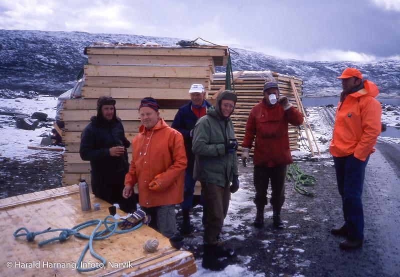 Medlemmer av Narvik og omegn turistforening på Skjomfjellet med materiell og hytteelementer som skal med helikopter inn til ny byggeplass, trolig på Skoaddejavrre. Prosjektleder Tore Martin Jakobsen med kopp foran munnen. Midt på med briller Helge Lagaard.