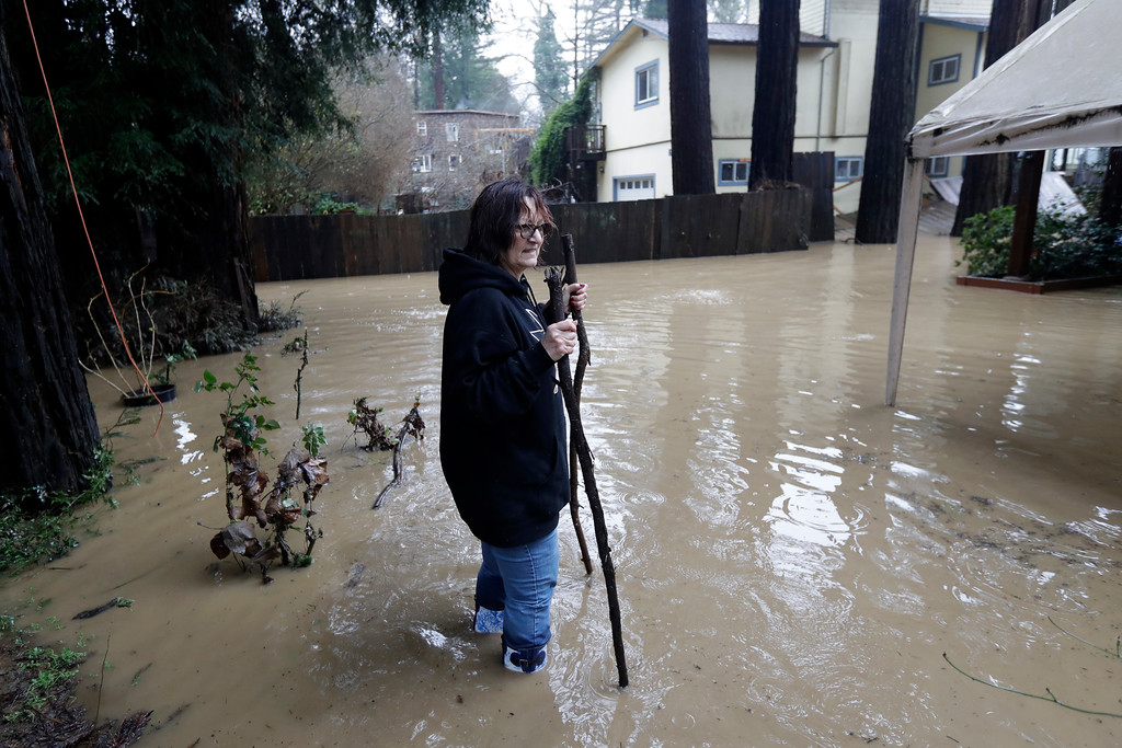 . Linda Forbes walks in a flooded property as she checks on a relative living in the neighborhood Tuesday, Feb. 7, 2017, in Felton, Calif. Flash flood watches are in place for parts of Northern California down through the Central Coast as heavy rains swamp roads and threaten to overtop rivers and creeks. (AP Photo/Marcio Jose Sanchez)