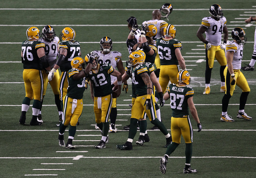 Description of . Brandon Jackson #32 and Aaron Rodgers #12 of the Green Bay Packers celebrate as the Packers defeat the Pittsburgh Steelers 31-25 to win Super Bowl XLV at Cowboys Stadium on February 6, 2011 in Arlington, Texas.  (Photo by Jonathan Daniel/Getty Images)