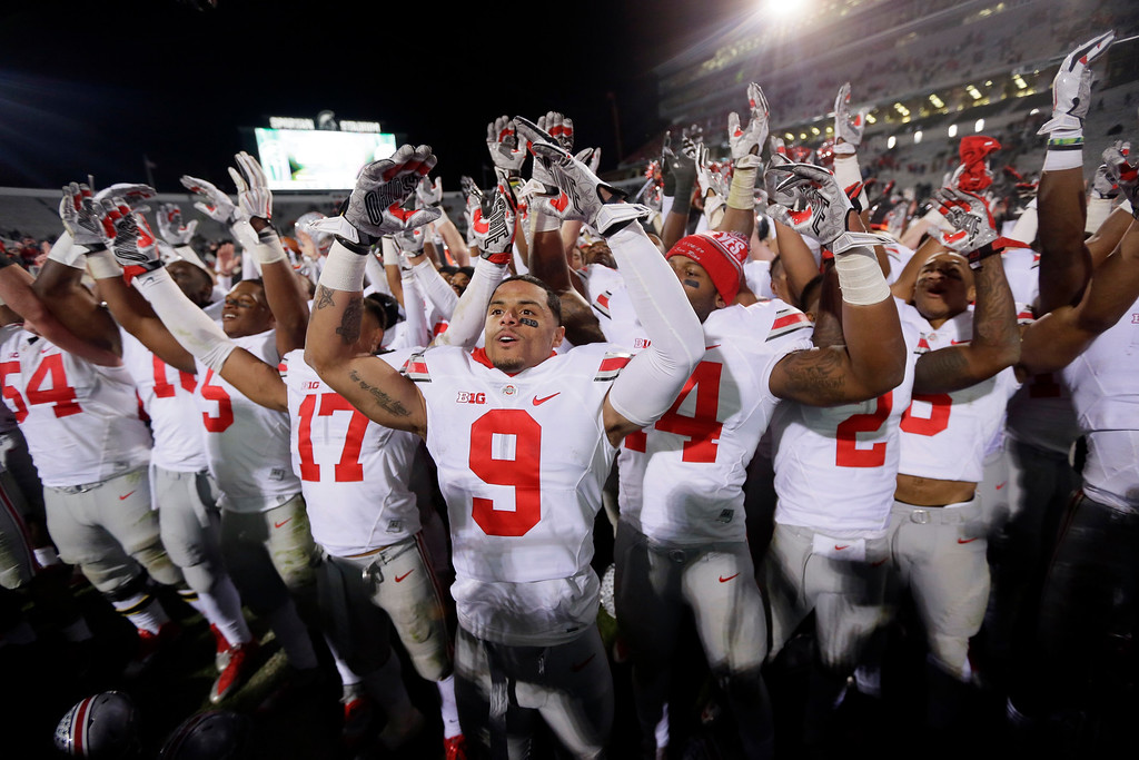 """. Ohio State wide receiver Devin Smith (9) and teammates sing \""""Carmen Ohio\"""" after they defeated Michigan State 49-37 in an NCAA college football game in East Lansing, Mich., Saturday, Nov. 8, 2014. (AP Photo/Carlos Osorio)"""