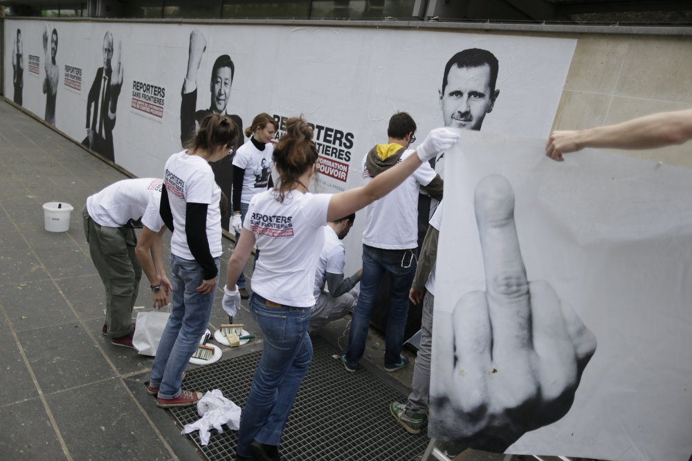 ". Activists of the international non-governmental organization ""Reporters sans frontiers\"" (Reporters without borders) set a poster bearing a picture of Syrian president Bashar al-Assad in Paris, on May 03, 2013, as they launch a campaign marking world press freedom day. The posters bears pictures of chiefs of state qualified by the organization as \""predators of Freedom of Information\"" gesturing angrily.  KENZO TRIBOUILLARD/AFP/Getty Images"