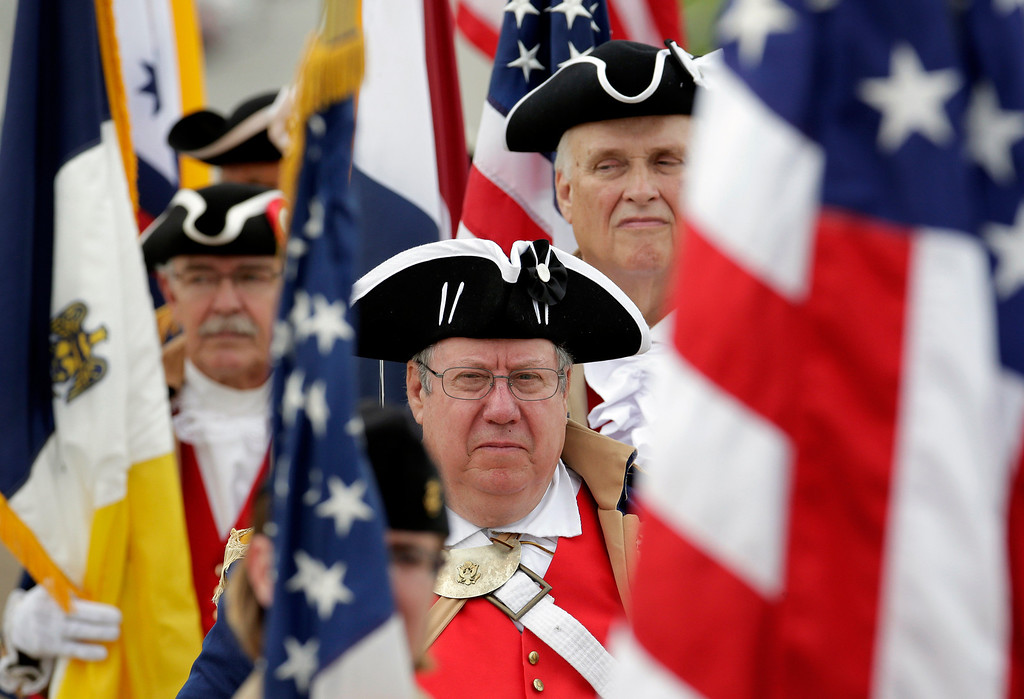 . Revolutionary War reenactors wait for the start of a Memorial Day observance at the National World War Museum at Liberty Memorial Monday, May 26, 2014, in Kansas City, Mo. (AP Photo/Charlie Riedel)