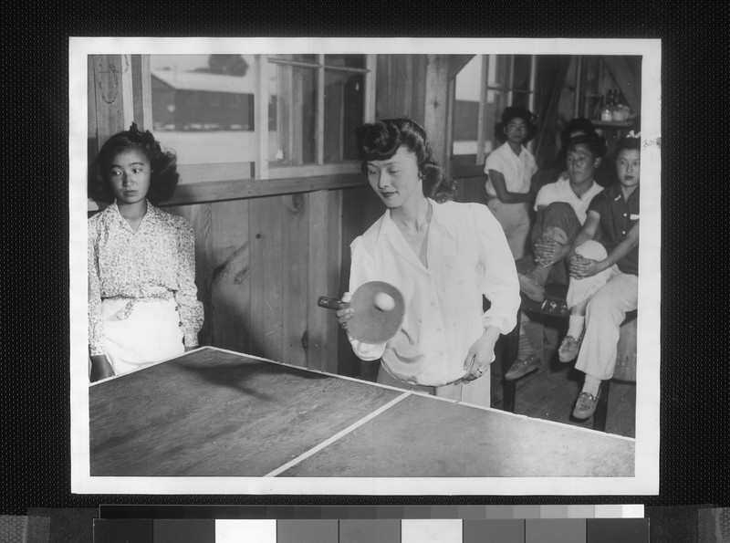 """""""How life goes between work hours, for Japanese evacuees now living at the Manzanar relocation center [...] Chikeyo Nakashima, a high school girl, playing table tennis in recreation hall"""" -- caption on photograph"""
