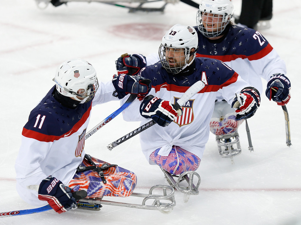 . Joshua Sweeney of USA (C) celebrates with teammate Tyler Carron (L) after scoring his team\'s first goal during the Ice Sledge Hockey Gold Medal match between Russia and USA at the Shayba Arena during day eight of the 2014 Paralympic Winter Games on March 15, 2014 in Sochi, Russia.  (Photo by Harry Engels/Getty Images)