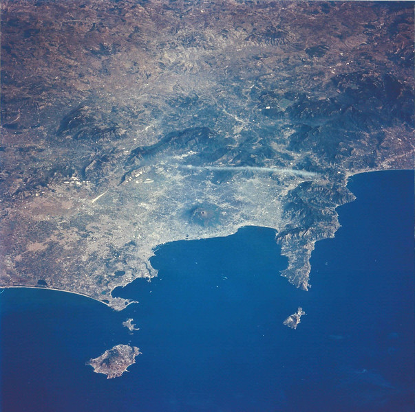 Astronaut Tom Jones: Oct. 10, 1994: We're on Endeavour (STS-68) over the Tyrrhenian Sea, west of Italy, looking down on the Bay of Naples and Mt. Vesuvius. That's Isla Ischia on the left, and Capri, the smaller island, on the lower right. Naples and its 3 million people lie on the left of the bay, to the northwest of Vesuvius. Herculaneum is almost directly below Vesuvius on the coast (where the town was buried by a pyroclastic flow in AD 79). Pompeii lies farther along the bay shore to the right. The circular depressions to the far left of the bay, near the sea, are the Phlegrean Fields, part of the caldera that makes up the bay region, near the town of Pozzuoli. On the peninsula to the right, in the circular bay, is Sorrento (full of lemon trees!). Naples is full of history, and the towns buried by Vesuvius are a treasure trove of ancient Roman life. Sorrento has superb views of Vesuvius and the Bay.