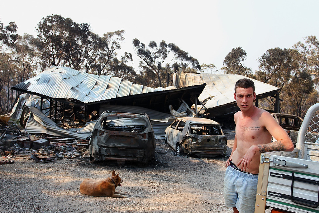 . A  young man stands in front of a family home business destroyed by bushfire as seen on October 21, 2013 in Yellow Rock, Australia.   (Photo by Lisa Maree Williams/Getty Images)