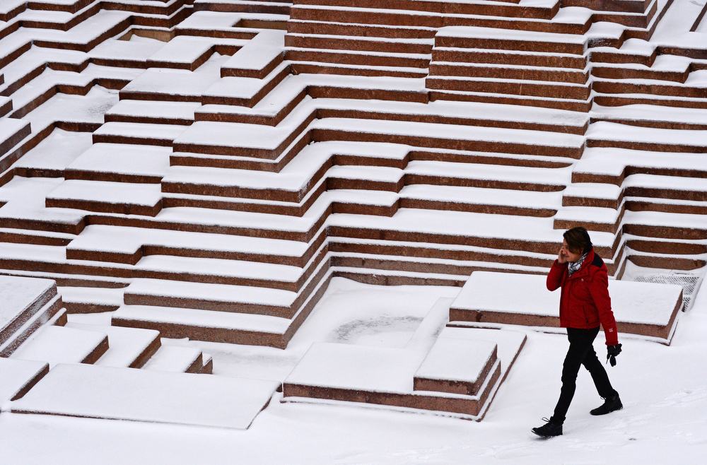 . Jesus Castillo walks in Skyline Park in downtown Denver after a few inches of snow fell overnight, January, 31 2014. A smaller storm will move back into the area later today. (Photo by RJ Sangosti/The Denver Post)