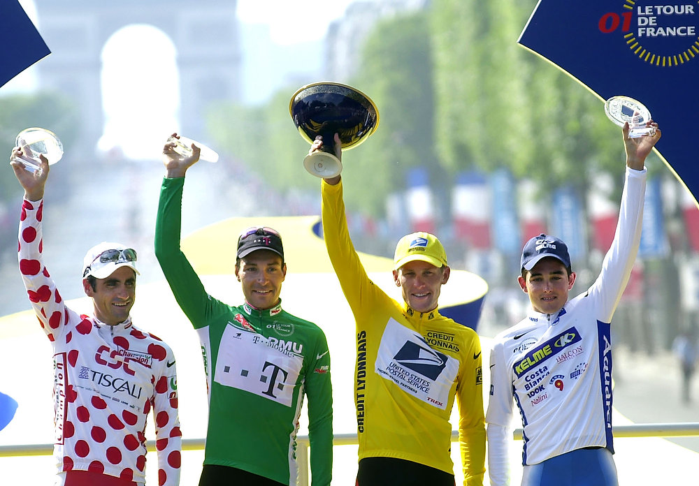 Description of . Race winner Lance Armstrong of Austin, Texas, (2nd from right), best sprinter Erik Zabel of Germany (2nd from left), best climber Laurent Jalabert of France (left) and best young rider Oscar Sevilla of Spain wave on the podium after the 20th and final stage of the Tour de France cycling race between Corbeil Essones and the Champs Elysees avenue in Paris on Sunday, July 29, 2001. (AP Photo/Christophe Ena)
