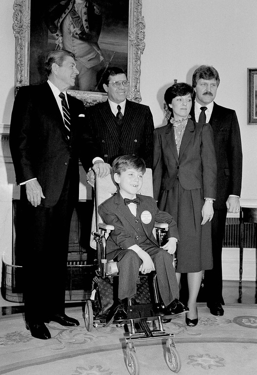 . Pres. Ronald Reagan, left, poses with Christopher Rush, the Muscular Dystrophy Poster Child, age 6 from Rochester, Mich., center, and his parents Richard and Dorie Rush MDA Chairman Jerry Lewis, center, Tuesday, in the Oval Office of the White House, April 5, 1983, Washington, D.C. Christopher has had the disease since nine months of age when it was diagnosed as Kugelberg-Welander disease. (AP Photo/Barry Thumma)