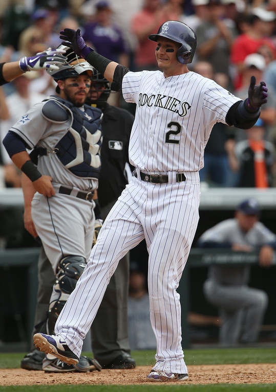 . Colorado Rockies\' Troy Tulowitzki, front, crosses home plate after hitting a solo home run as San Diego Padres catcher Rene Rivera looks on in the fifth inning of a baseball game in Denver on Sunday, May 18, 2014. (AP Photo/David Zalubowski)