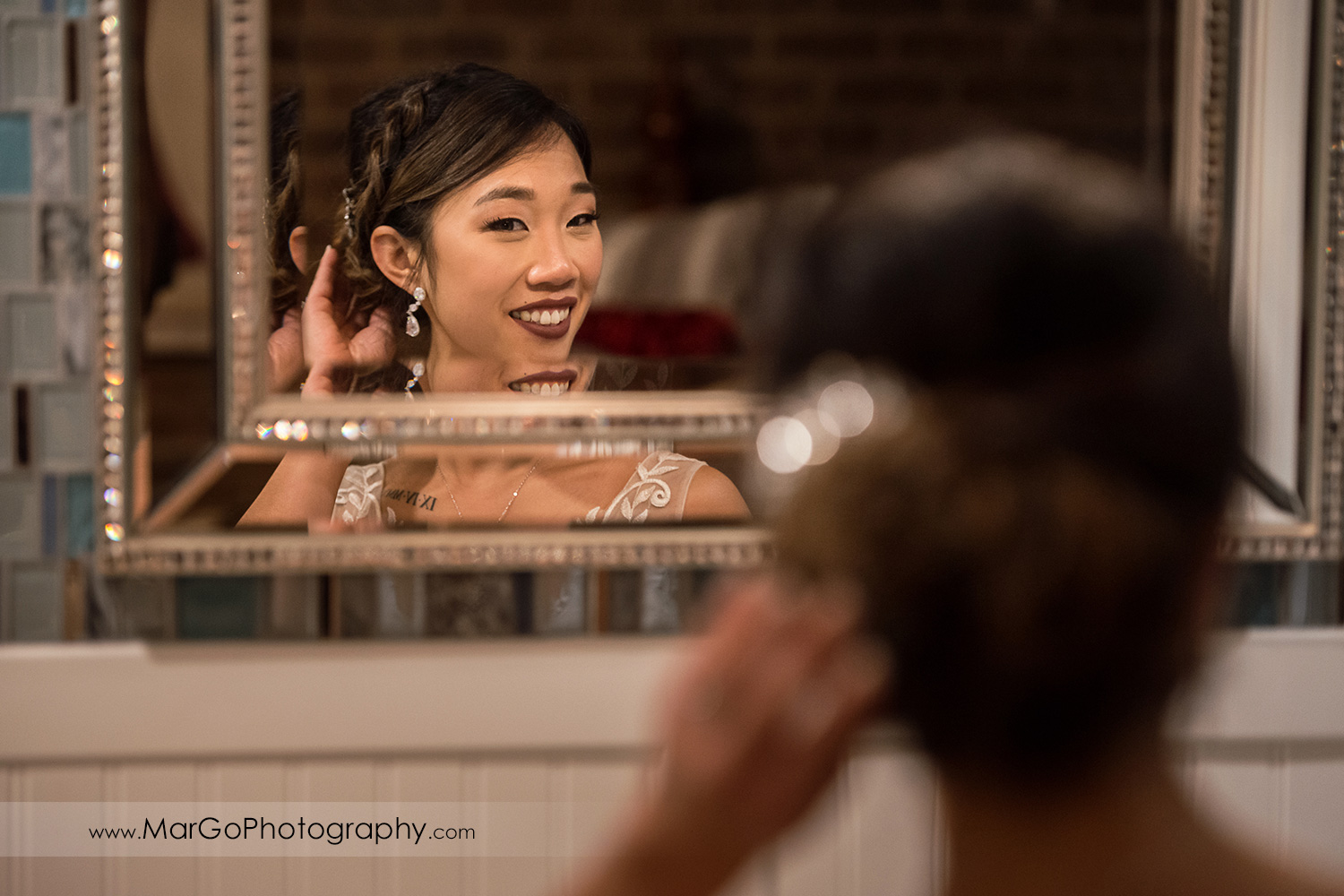 bride getting ready in front of the mirror at Sunol's Casa Bella bridal suite