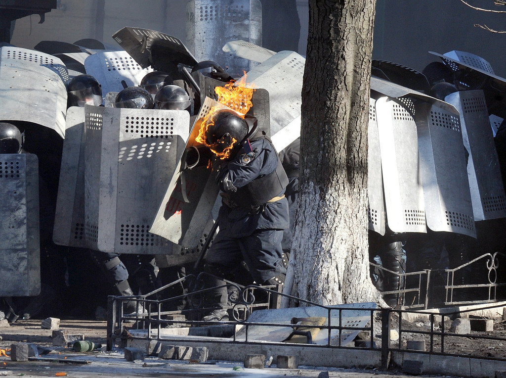 . A photo taken on Febraury 18, 2014 shows a riot police whose helmet is burning, shielding himself during clashes with anti-government protesters in central Kiev. At least five people were killed and scores injured on February 18 as anti-government protestors battled riot police in Kiev in the first outbreak of violence in weeks. Police said five civilians have died in clashes that prompted the city to shut down the subway system and issued a grave warning to protesters, with riot police troops massing near the Independence Square protest hub. AFP PHOTO/GENYA SAVILOV/AFP/Getty Images
