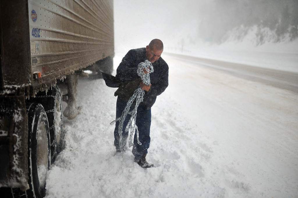 . TINY TOWN, CO. - MARCH 09: Truck driver Octabio Arellano put the chains on the tires during the trip from Center, CO. to Denver on north bound of Hwy 285 near the exit of Tiny Town. March 9, 2013. Tiny Town, Colorado. (Photo By Hyoung Chang/The Denver Post)