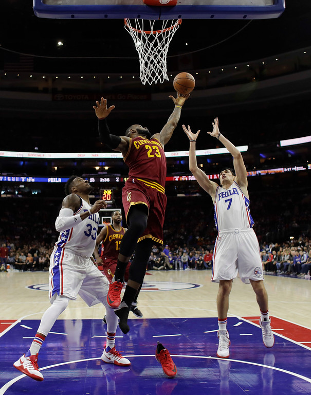. Cleveland Cavaliers\' LeBron James (23) leaps out of his shoe for a rebound against Philadelphia 76ers\' Ersan Ilyasova (7) and Robert Covington (33) during the second half of an NBA basketball game, Sunday, Nov. 27, 2016, in Philadelphia. (AP Photo/Matt Slocum)