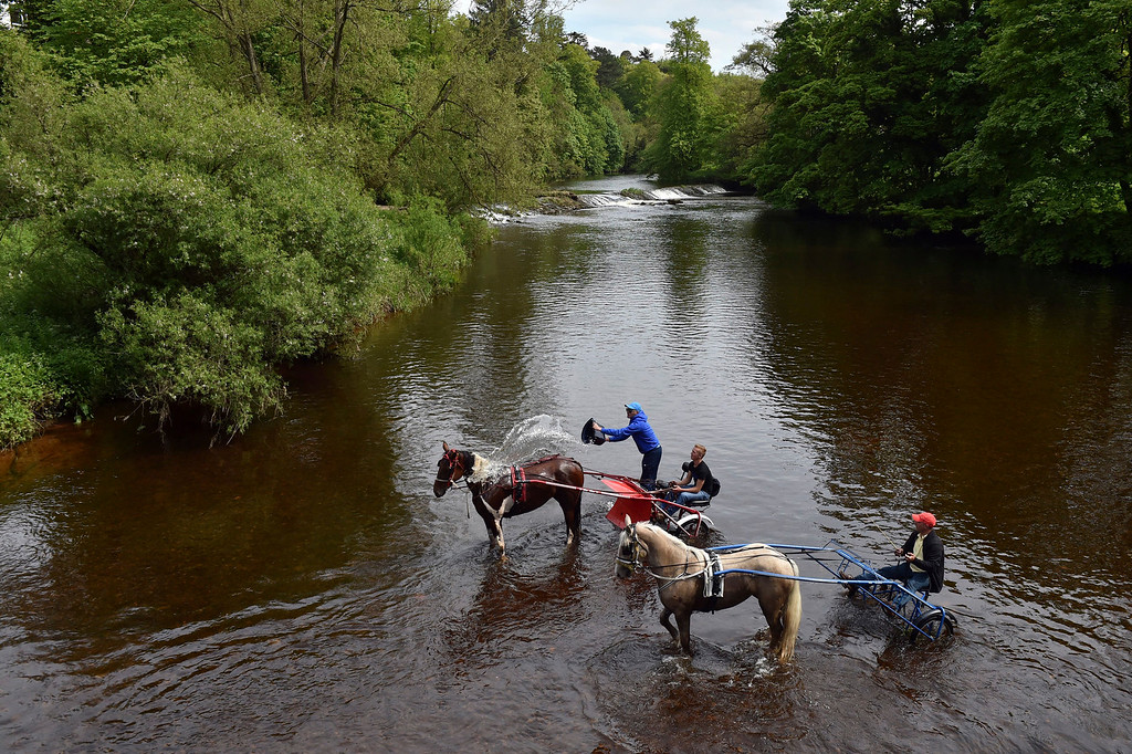 . Members of the traveller community take their horses and traps into the river Eden at the start of the Appleby Horse Fair, an annual gathering of gypsies and travelers in Appleby, Cumbria, England, Thursday, June 4, 2015. Owen Humphreys/PA Wire via AP)