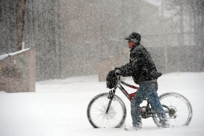 . A man pushes his bicycle through heavy snow near the intersection of Evans Ave. and Broadway in Denver, Colorado, Sunday morning, February 24th, 2013.  (Photo By Andy Cross / The Denver Post)