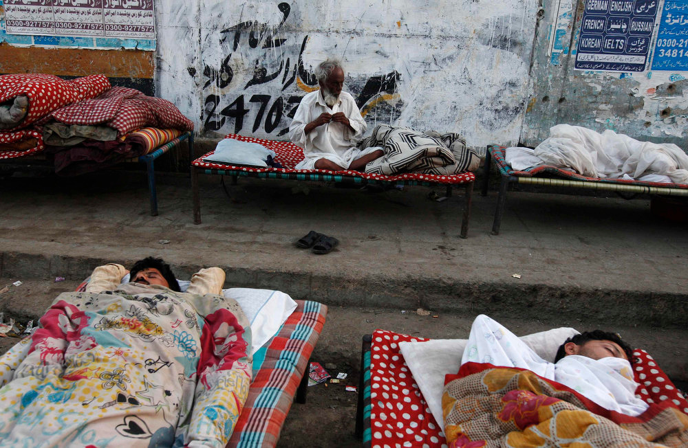 . An elderly man buttons his shirt on a charpoy bed along a road near a railway station in Karachi April 1, 2013. Charpoy bed guesthouses are only set up at night from 9pm to 7am for the homeless, passengers and drivers, charging about 40 Pakistani rupees ($0.40) per night. REUTERS/Akhtar Soomro
