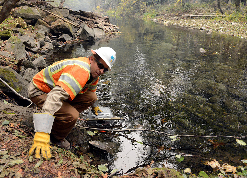 . PG&E worker Frank Linnenbrink loads a spray tank with water from the Big Sur River while setting up defenses near a pole along the river as firefighters battle a wildland fire in the Pfeiffer Ridge area in Big Sur on Monday December 16, 2013. (Photo David Royal/ Monterey County Herald)