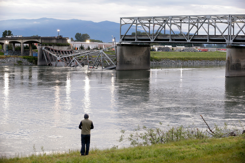 . A person looks from the south bank of the Skagit River across to the collapsed portion of the Interstate 5 bridge Friday, May 24, 2013, in Mount Vernon, Wash. A truck carrying an oversize load struck the four-lane bridge on the major thoroughfare between Seattle and Canada, sending a section of the span and two vehicles into the Skagit River below Thursday evening. All three occupants suffered only minor injuries. At an overnight news conference, Washington State Patrol Chief John Batiste blamed the collapse on a tractor-trailer carrying a tall load that hit an upper part of the span. (AP Photo/Elaine Thompson)