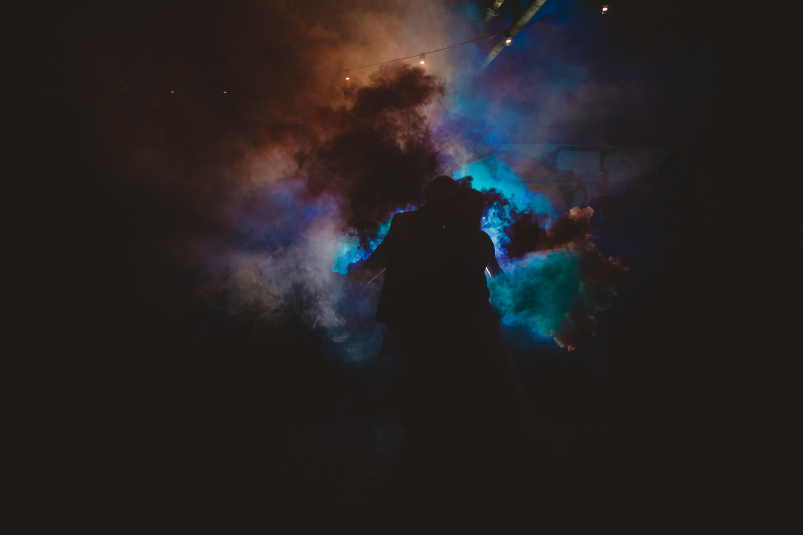 bride and groom kissing on their wedding reception danceflore as they hold smoke grenedes that silloutte the entire venue in blue light through the smoke