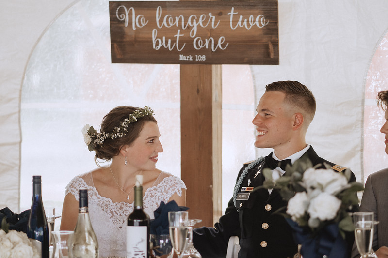 Bride and groom smile at each other while sitting at their table.