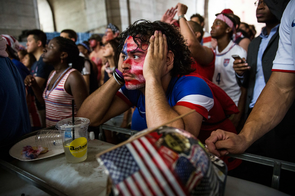 . Christian Raja, of Brooklyn, reacts while watching the United States versus Belgium game in the World Cup on a projected screen under the Manhattan Bridge on July 1, 2014 in the Dumbo neighborhood of the Brooklyn borough of New York, United States. Belgium went on to eliminate the U.S. from the World Cup in overtime with a final score 2-1.  (Photo by Andrew Burton/Getty Images)