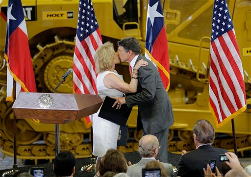 Description of . Texas Gov. Rick Perry kisses his wife, Anita at Holt Cat, Monday, July 8, 2013, in San Antonio, Texas where announced he will not seek reelection. A staunch Christian conservative, proven job-creator and fierce defender of states' rights, Perry has been in office nearly 13 years, making him the nation's longest-sitting current governor. (AP Photo/Eric Gay)