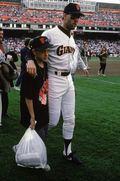 . Will Clark #22 of the San Francisco Giants and his son gather on the field after a 6.9 magnitude earthquake struck the Bay Area, postponing Game three of the 1989 World Series against the Oakland Athletics at Candlestick Park on October 17, 1989 in San Francisco, California.  (Photo by Otto Greule Jr/Getty Images)