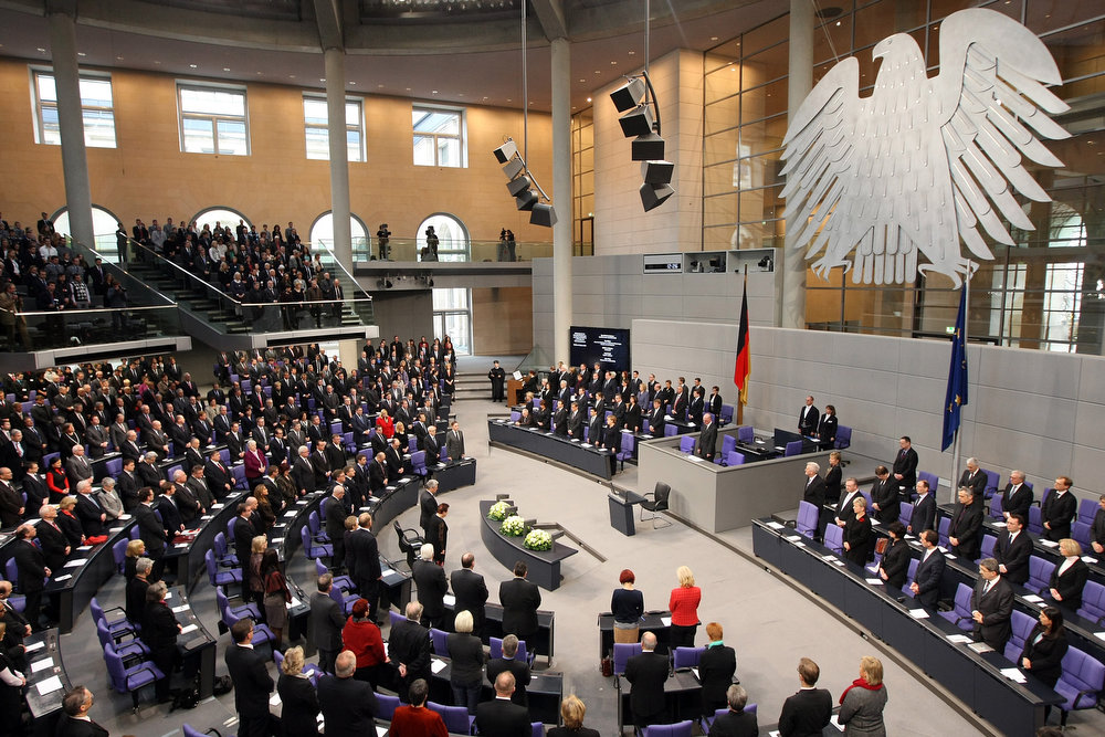 Description of . A general view shows German Chancellor Angela Merkel (C, R), members of German government and parliament standing as a cantor sings at the German lower house of Parliament Bundestag, in Berlin on January 30, 2013 during a memorial held by deputies for the victims of the Nazi regime, and the anniversary of the liberation of Auschwitz concentration camp on January 27, 1945. Since the date fell on a Sunday this year, the event was held later, on the day marking 80 years since Adolf Hitler became chancellor.  ADAM BERRY/AFP/Getty Images