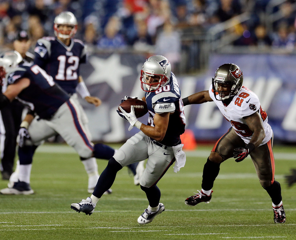 . New England Patriots wide receiver Danny Amendola (80) catches a pass from quarterback Tom Brady (12) in front of Tampa Bay Buccaneers cornerback Leonard Johnson (29) and heads for the goal for the first touchdown of the NFL preseason game in the first quarter Friday, Aug. 16, 2013, in Foxborough, Mass. (AP Photo/Charles Krupa)