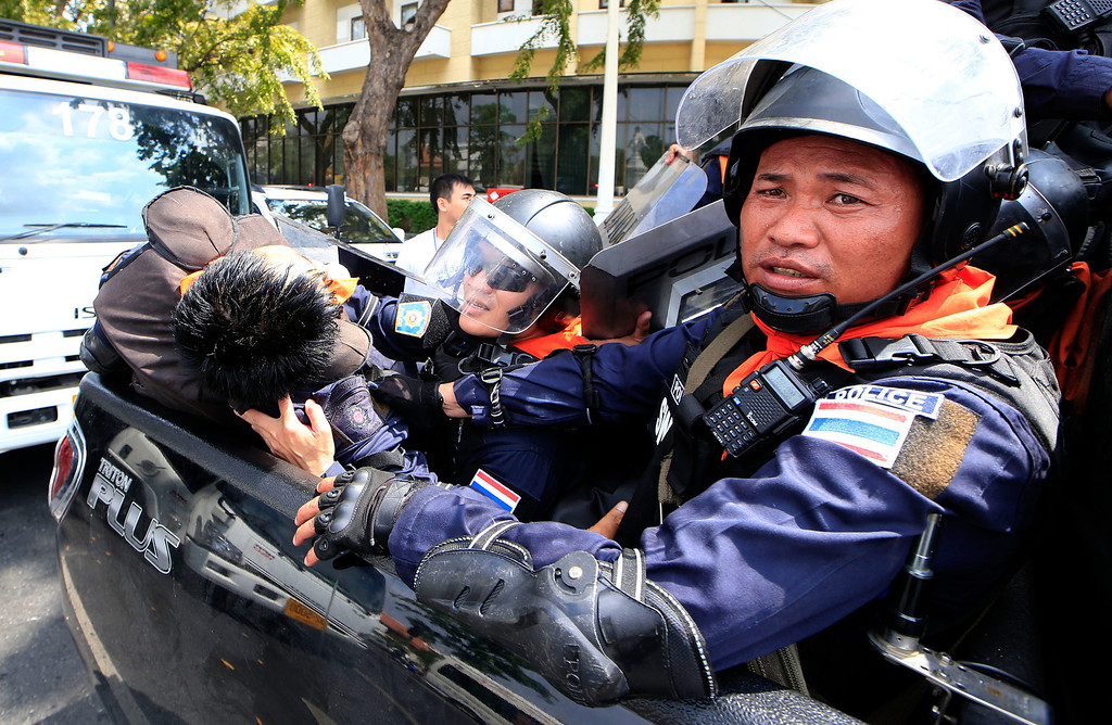 . Thai policemen with their injured colleague, left, retreat after a clash between police force and anti-government protesters Tuesday, Feb. 18, 2014 in Bangkok, Thailand.  (AP Photo/Wason Wanichakorn)