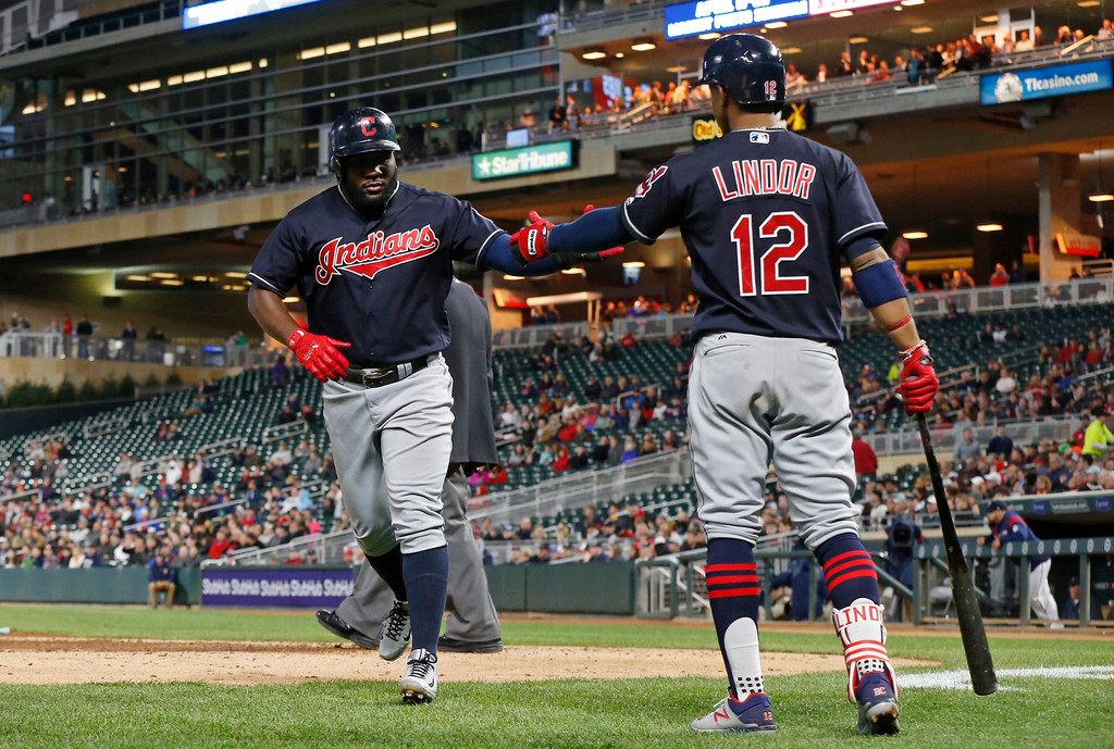 . Cleveland Indians\' Albraham Almonte, left, is greeted by Francisco Lindor after scoring against the Minnesota Twins during the fourth inning of a baseball game Tuesday, April 18, 2017, in Minneapolis. (AP Photo/Jim Mone)