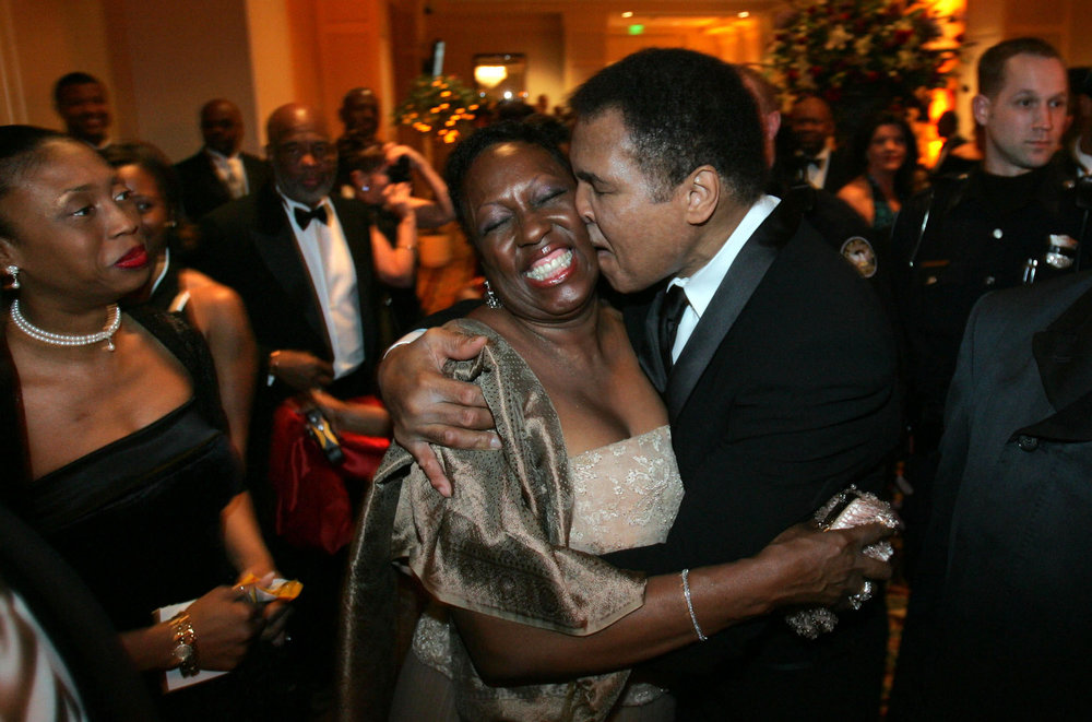 Description of . Muhammad Ali, right, stops to give a hug to fan Martha Thomas as he arrives for the Butterfly Ball, a tribute in his honor, coinciding with Black History Month, Saturday Feb. 26, 2005, in Atlanta. (AP Photo/John Amis)