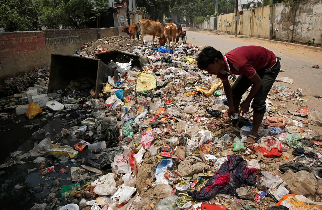 ". An Indian rag picker looks for reusable material on a mound of garbage filled with plastic bags by the side of a road side in Allahabad, India, Monday, June 4, 2018. The theme for this year\'s World Environment Day, marked on June 5, is ""Beat Plastic Pollution.\"" (AP Photo/Rajesh Kumar Singh)"
