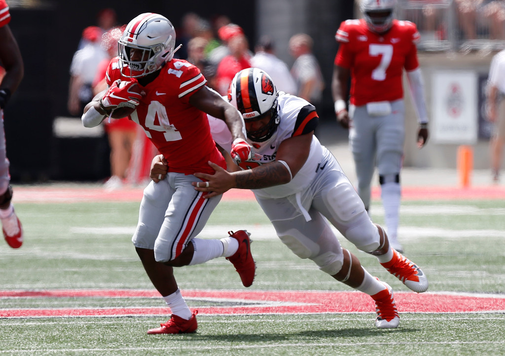 . Ohio State receiver K.J. Hill tries to get away from Oregon State defensive lineman Kalani Vakameilalo during the first half of an NCAA college football game Saturday, Sept. 1, 2018, in Columbus, Ohio. (AP Photo/Jay LaPrete)