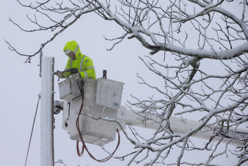 . A Worker repairs power lines during a winter storm, Tuesday, March 13, 2018, in Norwell, Mass. The nor\'easter is expected to deliver up to 2 feet of snow to some areas of New England. (AP Photo/Steven Senne)